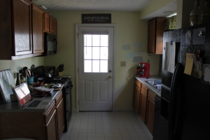 "The before!  Yellow walls, oak cabinets and bad fake ""tin"" backsplash on one side."