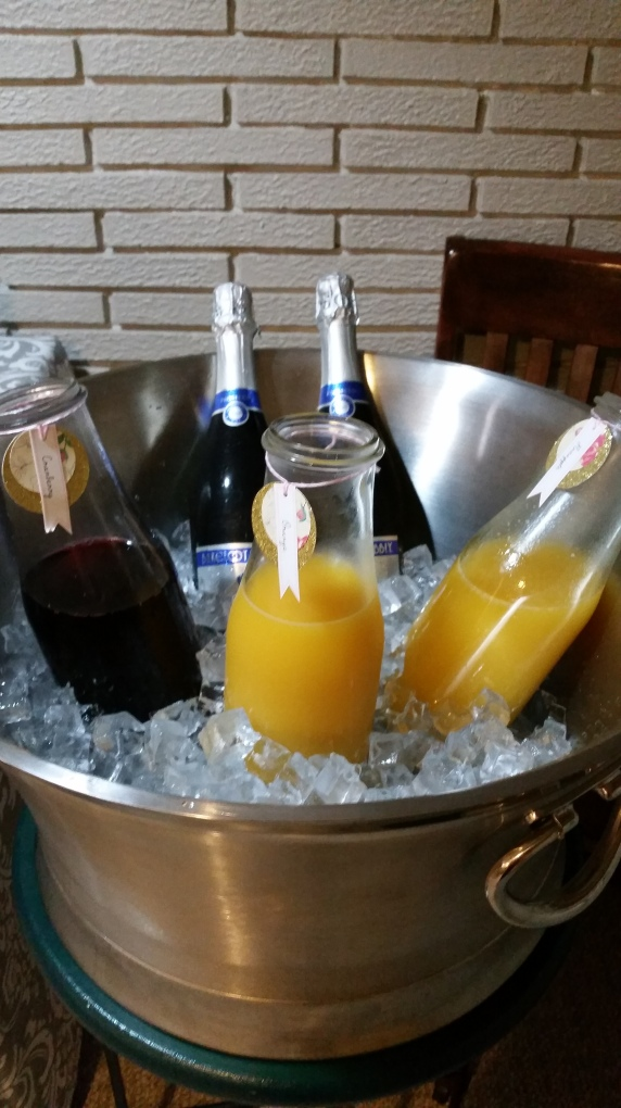 Carafes of juice and bottles of champagne chill nearby